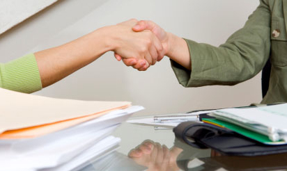 2 people shaking hands over a stack of papers and folders